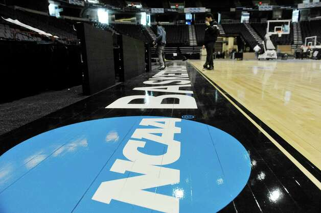 With the floor in place workers continue to set up  for the women's NCAA basketball tournament this weekend on Wednesday, March 25, 2015, in Albany, N.Y.   The floor is made special just for this regional tournament.  Monday night after the game the crews will get right back to work taking the floor apart and setting up for ice hockey.  (Paul Buckowski / Times Union) Photo: PAUL BUCKOWSKI / 00031176A