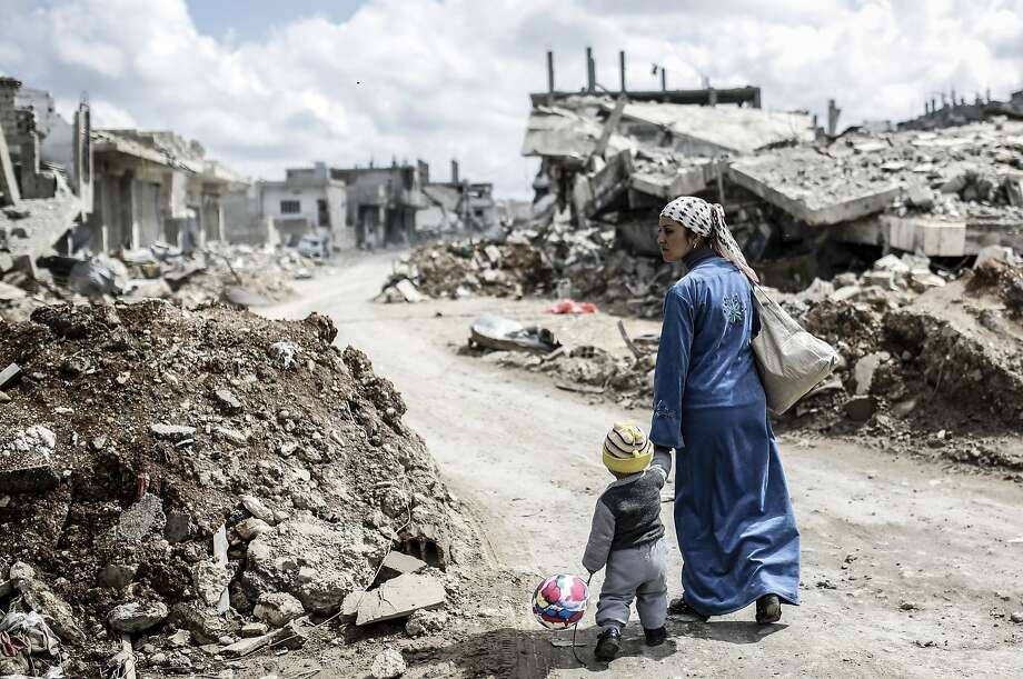 TOPSHOTS A Kurdish Syrian woman walks with her child past the ruins of the town of Kobane, also known as Ain al-Arab, on March 25, 2015. Islamic State (IS) fighters were driven out of Kobane on January 26 by Kurdish and allied forces. AFP PHOTO/YASIN AKGULYASIN AKGUL/AFP/Getty Images Photo: Yasin Akgul, AFP / Getty Images