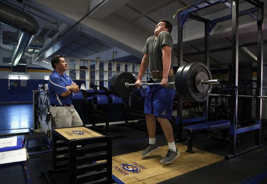 Junipero Serra High School football player Jack Dreyer (right) jump shrugs more than 240 pounds as head coach Patrick Walsh checks his form during a workout session at the school's weight room, Wednesday, March 25, 2015, in San Mateo, Calif. Dreyer, age 17, who is 6 feet 8 inches tall, weighs almost 300 pounds and has a 4.25 GPA, has signed with Stanford with a full scholarship to play outside tackle. Photo: Santiago Mejia, The Chronicle