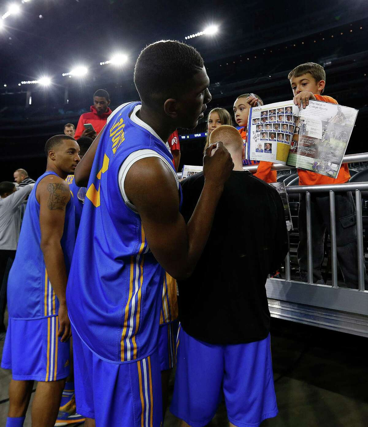 UCLA Bruins forward Kevon Looney (5) signs autographs for fans along with other teammates after their shoot around at NRG Stadium, Thursday, March 26, 2015, in Houston.