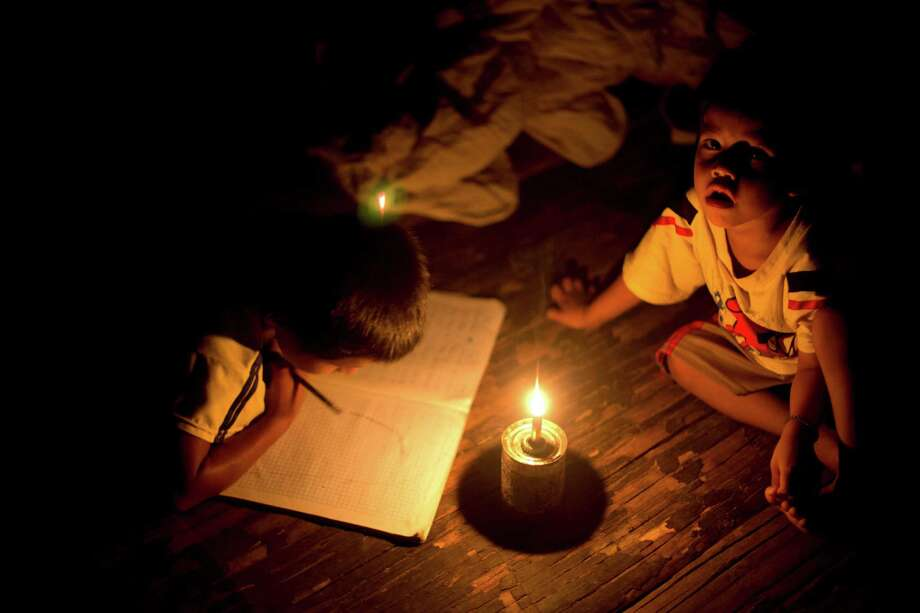 In this March 16, 2015 photo, Pedro Tello draws for fun in his notebook as his younger brother Felix hangs out with him inside their home, illuminated by a candle on a tin can, serving as a makeshift candle holder, in the Ashaninka Indian hamlet of Saweto, Peru. Both boys attend school in the same one-room hut. (AP Photo/Martin Mejia) Photo: Martin Mejia / Associated Press / AP