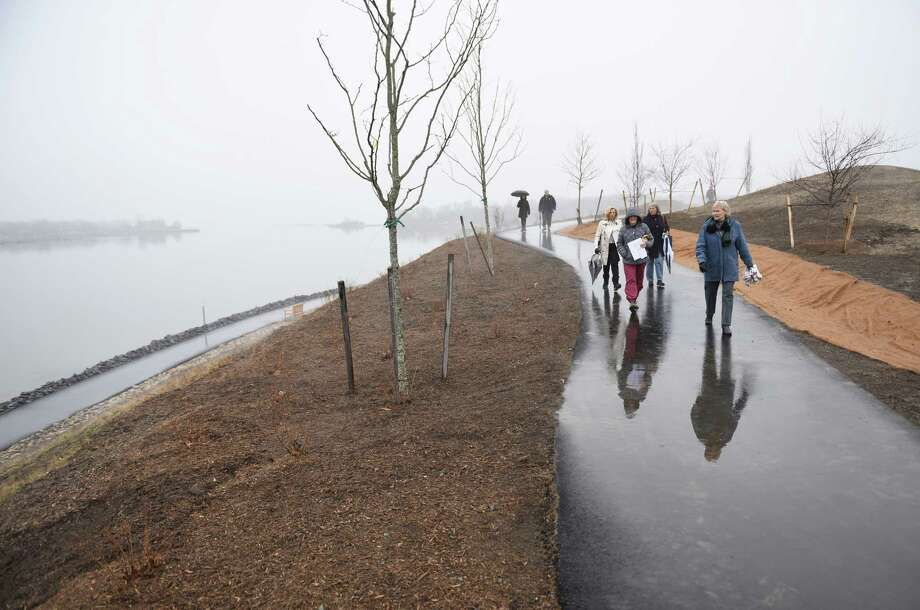 Folks walk along the paved walking paths at the new Cos Cob Park in the Cos Cob section of Greenwich, Conn. Thursday, March 26, 2015.  The park was officially dedicated Thursday and features a panoramic view of the Long Island Sound, a synthetic turf field, an open air pavilion shelter, a children's playground, walking paths with benches, restrooms, an open air patio with stadium seating and sidewalks connecting the park to the nearby Cos Cob Metro-North station parking lot. Photo: Tyler Sizemore / Greenwich Time