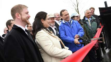 Park development team members Jason kaufman, left, and Project Manager Gabriella Circosta stand beside First Selectman Peter Tesei as he cuts the ribbon for the new Cos Cob Park in the Cos Cob section of Greenwich, Conn. Thursday, March 26, 2015.  The park was officially dedicated Thursday and features a panoramic view of the Long Island Sound, a synthetic turf field, an open air pavilion shelter, a children's playground, walking paths with benches, restrooms, an open air patio with stadium seating and sidewalks connecting the park to the nearby Cos Cob Metro-North station parking lot.