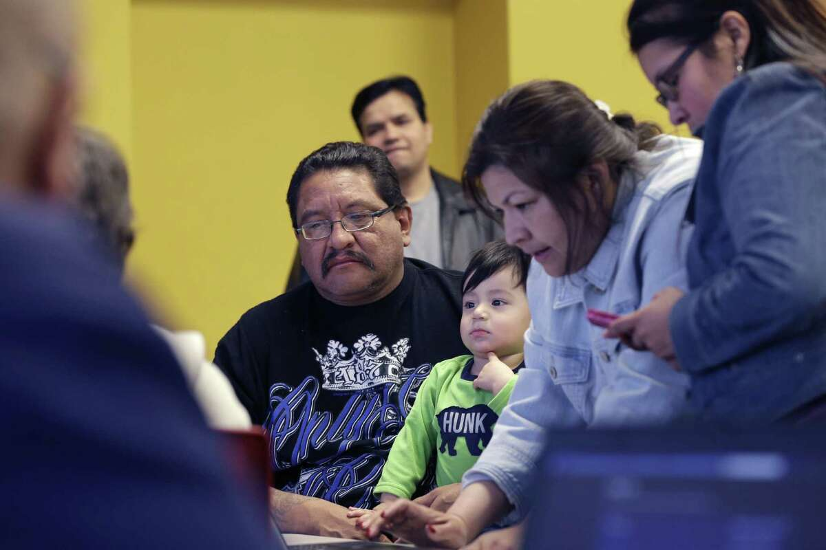 FILE - In this Feb. 12, 2015 file photo, Fred Cardenas, center, holds his grandson, thirteen-month-old Luis Del Angel, as JPS Health Network patient navigator Delaila Hernandez works on a laptop during a Affordable Care Act enrollment event at the Fort Worth Public Library in Fort Worth, Texas. With more than 1 million Texans enrolled for health insurance through the federal marketplace, Affordable Care Act assisters are turning their focus to educating Latinos and young childless adults ahead of the next enrollment period and getting out the message that hundreds of thousands of Texas children are eligible for Medicaid. (AP Photo/LM Otero, File)