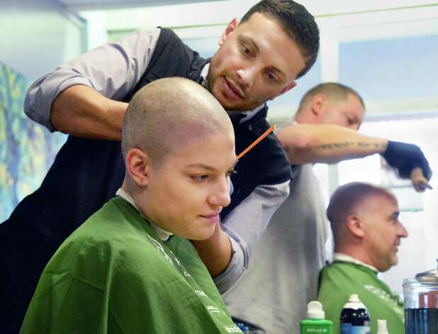Community volunteer Claire Wilks of Ballston Spa, and Saint Rose lacrosse coach Jim Morrissey have their heads shaved by  barbers Sammy Styles, standing left, and Josh Shadick of Sammy Styles Barber Shop during the St. Baldrick's Foundation fundraiser to find cures for childhood cancers at the College of Saint Rose Thursday March 26, 2015, in Albany, NY. (John Carl D'Annibale / Times Union) Photo: John Carl D'Annibale / 00031166A