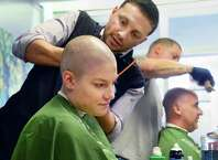 Community volunteer Claire Wilks of Ballston Spa, and Saint Rose lacrosse coach Jim Morrissey have their heads shaved by  barbers Sammy Styles, standing left, and Josh Shadick of Sammy Styles Barber Shop during the St. Baldrick's Foundation fundraiser to find cures for childhood cancers at the College of Saint Rose Thursday March 26, 2015, in Albany, NY. (John Carl D'Annibale / Times Union)