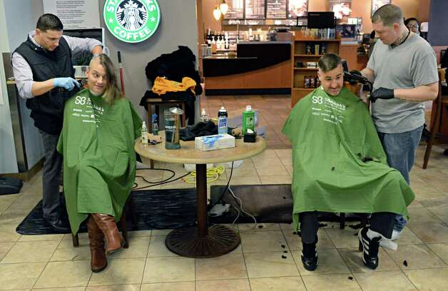Barbers Sammy Styles, left, and Josh Shadick of Sammy Styles Barber Shop shave the heads of community volunteer Claire Wilks of Ballston Spa, and Saint Rose lacrosse coach Jim Morrissey during the Saint Baldrick's Foundation fundraiser to find cures for childhood cancers at the College of Saint Rose Thursday March 26, 2015, in Albany, NY.  (John Carl D'Annibale / Times Union) Photo: John Carl D'Annibale / 00031166A