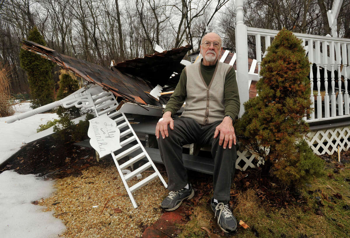 Tony Paolitto poses on the steps of his hand-built gazebo that now lays in ruins in his back yard in Stamford, Conn., on Thursday, March 26, 2015. Paolitto, a retired engineer, said the weight of this winter's snow was the cause of the destruction.