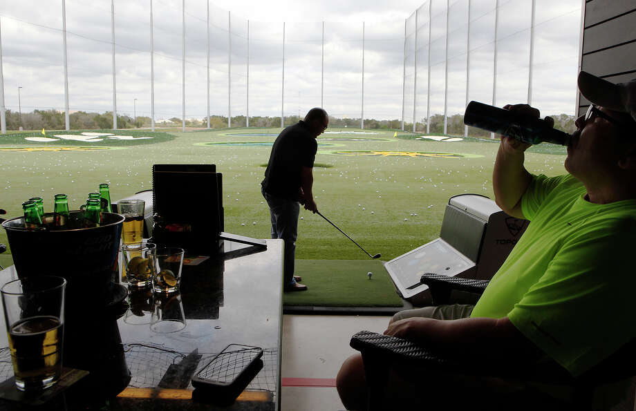 Frankie Covarrubia prepares to hit a golf ball as Phillip Covarrubia and Ron Rodriguez (not seen) watch at Topgolf. The men said Topgolf is a casual, social place unlike actually being on a golf course, where at times you have to be really quiet or people could shush you. They also compared it to being somewhat like bowling, where you can have drinks, go for your turn, and then come back to your table. Topgolf had more than $700,000 in drink sales last month making the venue the 11th top-selling in the state and the fourth top spot in Bexar County. Topgolf opened on Jan. 30 of this year. Photo: Cynthia Esparza /For The Express-News / For the San Antonio Express-News