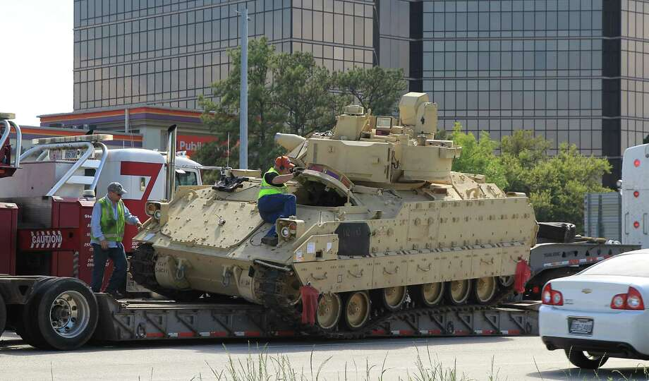 Workers prepare to reload an armored military vehicle on to a trailer after the vehicle shifted on the trailer on IH 610 North just west of Shepherd Thursday, March 26, 2015, in Houston. Photo: James Nielsen, Houston Chronicle / © 2015  Houston Chronicle