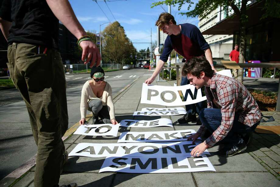 Peregrine Church, right, creates a Rainwork, a rain-activated message, with friends, from left, Forest Tresidder, Lydia Warren and Xack Fischer on a sidewalk in Seattle's University District. Church's creations have gone viral on the Internet after a video of his fun messages was shared online. Photographed on Thursday, March 26, 2015. Photo: JOSHUA TRUJILLO, SEATTLEPI.COM / SEATTLEPI.COM