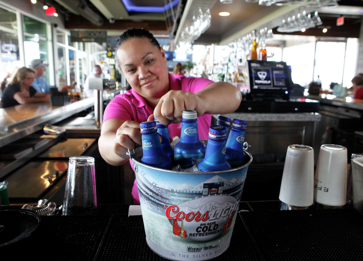 TopGolf bartender Marina Amaya opens the tops of beer bottles that had been ordered on March 25, 2015.