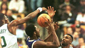 BOSTON, :  Kobe Bryant of the Los Angeles Lakers (C) drives against Ron Mercer (R) and Walter McCarty of the Boston Celtics 26 November at the Fleet Center in Boston, MA.  AFP PHOTO/John MOTTERN (Photo credit should read JOHN MOTTERN/AFP/Getty Images)
