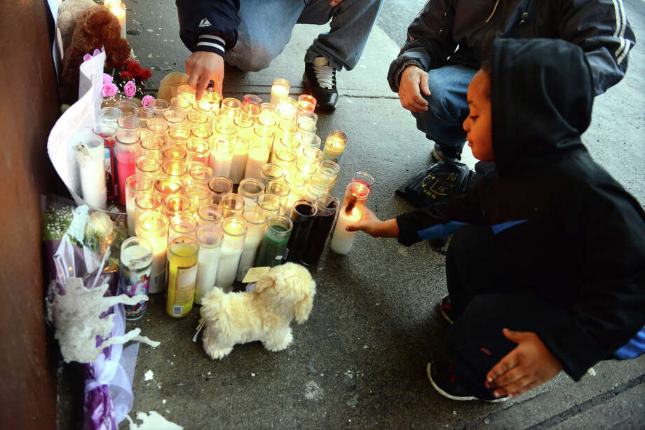 Cinsere Brooks, 6, places a candle at a memorial in front of T. Market along Reservoir Avenue in Bridgeport, Conn., on Thursday Mar. 26, 2015. The market's store clerk Hakeem Joseph was shot and killed there on Wednesday. A second murder occured nearby on Chopsey Hill Road today, in which Jose Araujo was shot while working at a construction site. Photo: Christian Abraham / Connecticut Post