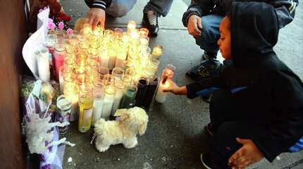 Cinsere Brooks, 6, places a candle at a memorial in front of T. Market along Reservoir Avenue in Bridgeport, Conn., on Thursday Mar. 26, 2015. The market's store clerk Hakeem Joseph was shot and killed there on Wednesday. A second murder occured nearby on Chopsey Hill Road today, in which Jose Araujo was shot while working at a construction site.