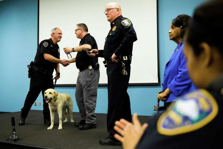 Onlookers watch as Dennis, a 6-year bomb-sniffing veteran member of the Seattle Police Department enters into retirement from his place at the side of faithful handler, K-9 officer Craig Williamson.