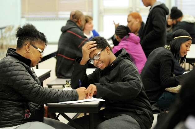 Tierra Mathias, left, fills out paperwork for her son Shann Stallworth, 13, center, who'll be a freshman next school year, on Thursday, March 26, 2015, at Bishop Maginn in Albany, N.Y. (Cindy Schultz / Times Union) Photo: Cindy Schultz / 00031194A