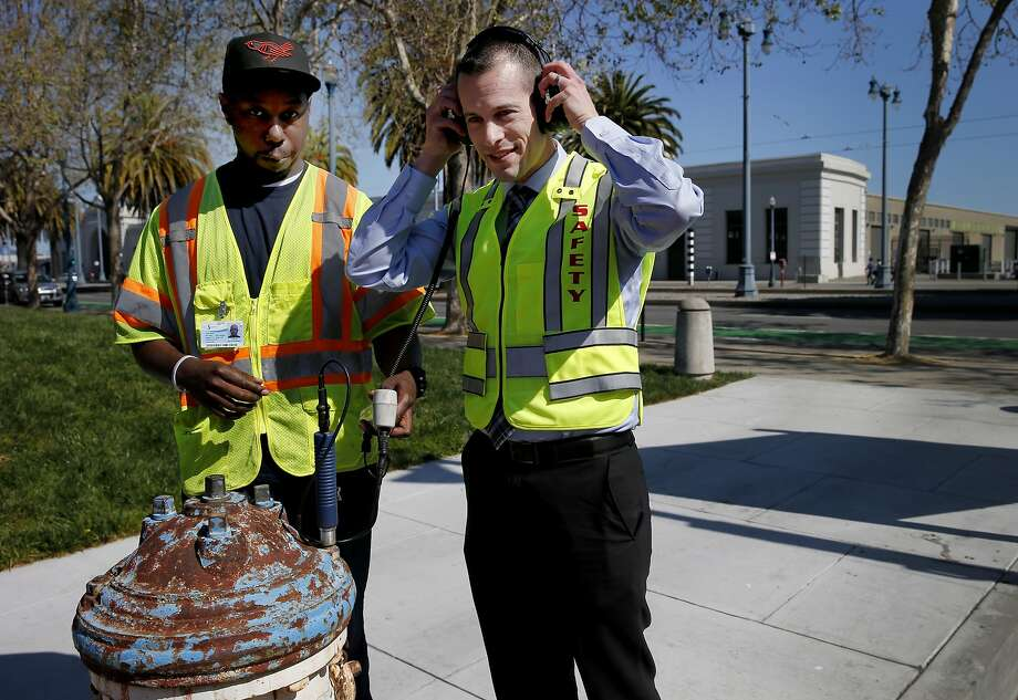 Water technician John Bess (left) and Adam McKnight of Pure Technologies listen to a leak which can be heard in a hydrant installed in 1909. San Francisco, Calif. water officials are employing some new high technology to detect leaks in the city's aging underground pipes and hydrants. Photo: Brant Ward, The Chronicle