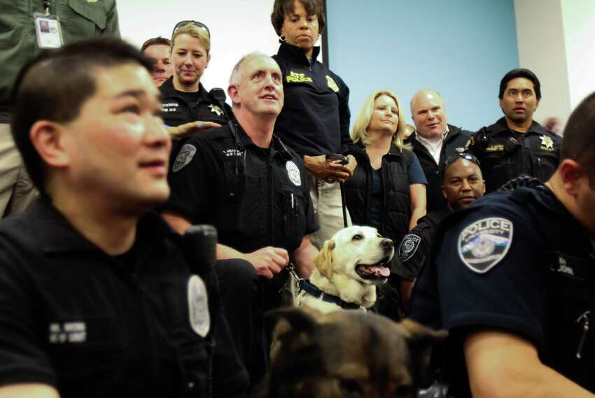 K-9 officer Craig Williamson and his bomb-sniffing dog Dennis pose for a picture among other K-9 handlers and their dogs as Dennis entered into retirement after six years of service. The retiring yellow Labrador Retriever was recently diagnosed with terminal cancer, and is expected to live another six to 12 months. Photo taken on March 26, 2015.