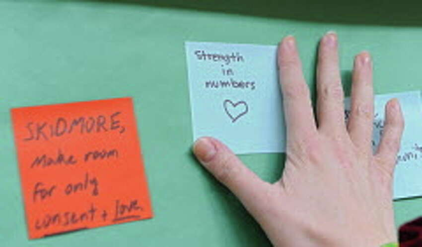 A student puts a sticky note on a wall during a silent rally to protest a college readmission hearing for a male student who was suspended for a year for sexually assaulting Skidmore College student Reina Keifer at Skidmore College on Friday, March 13, 2015 in Saratoga Springs, N.Y. (Lori Van Buren / Times Union)