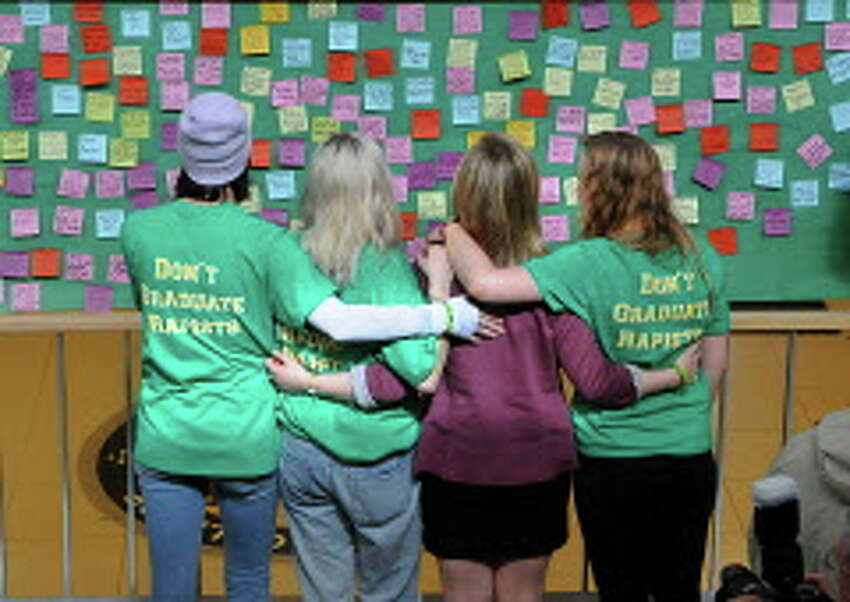 Skidmore College student Reina Keifer, second from right, stands with her best friends, from left, Emma Cushing, Izzy Howard and Katie Plowwright as they look at a message board during a silent rally at Skidmore College on Friday, March 13, 2015 in Saratoga Springs, N.Y. The rally was to protest a college readmission hearing for a male student who was suspended for a year for sexually assaulting Keifer. (Lori Van Buren / Times Union)