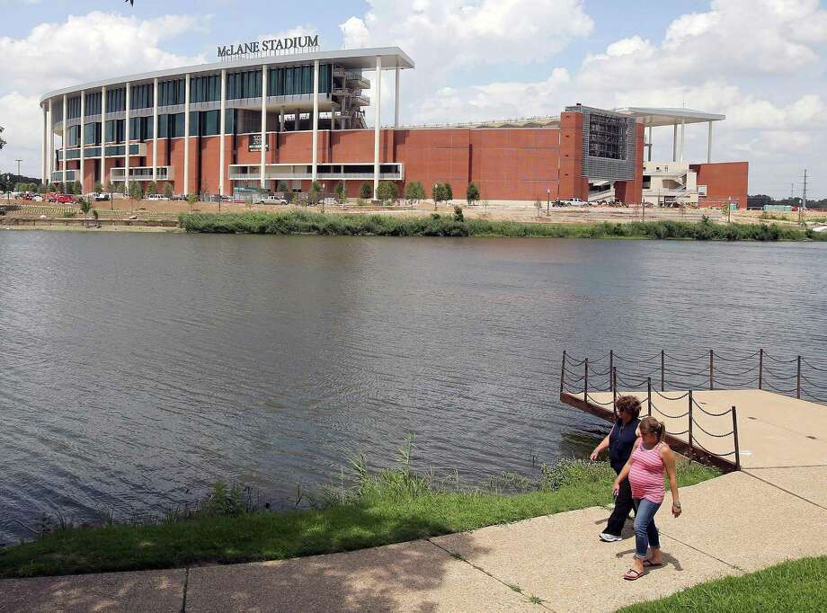 FILE - In this July 2, 2014, file photo, people stroll along the river walk across from the new McClane Stadium at Baylor University in Waco, Texas. The $260 million stadium located near campus on the Brazos river debuts at the end of the month and replaces the  64-year-old Floyd Casey Stadium. (AP Photo/Waco Tribune Herald, Jerry Larson, File) Photo: Jerry Larson, MBO / Waco Tribune Herald