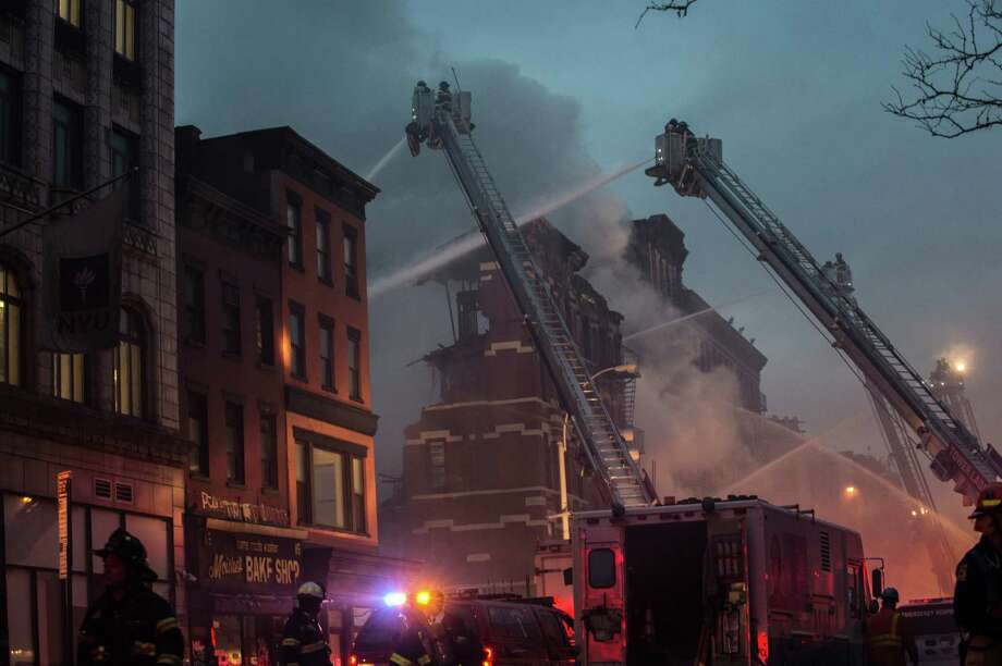 Firefighters work to contain a seven-alarm fire in the East Village neighborhood of New York, March 26, 2015. A powerful explosion, likely gas-related, and subsequent fire caused two buildings to collapse, leaving a dozen or more people injured -- at least three of them critically. (Robert Stolarik/The New York Times) ORG XMIT: XNYT124 Photo: ROBERT STOLARIK / NYTNS