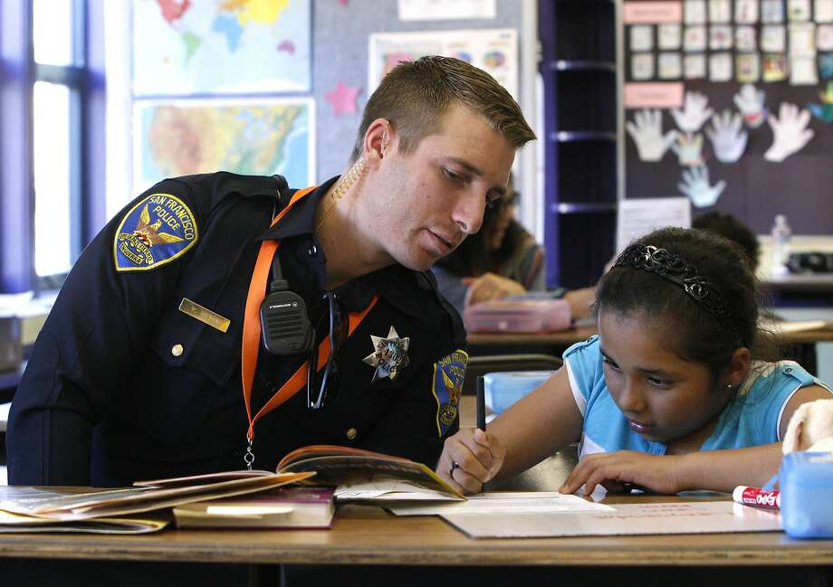 S.F. police officer Kyle Wren checks the spelling of 11-year-old Adriana Rodriguez, who is in the third grade at Bret Harte Elementary, at the school's Reading Parters program, Thursday, March 26, 2015, in San Francisco, Calif. Photo: Santiago Mejia, The Chronicle