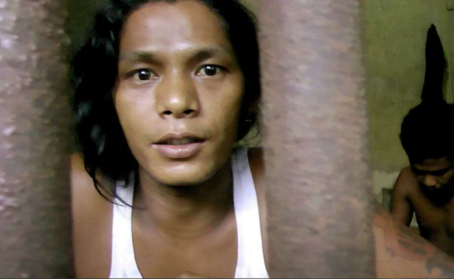 """In this Thursday, Nov. 27, 2014 image from video, Kyaw Naing, a slave from Myanmar, looks through the bars of a cell at the compound of a fishing company in Benjina, Indonesia. After working for three years on a Thai trawler, sometimes enduring beatings with the bones of sting ray, he begged his captain to let him return home. """"All I did was tell my captain I couldn't take it anymore, that I wanted to go home,"""" Naing says. """"The next time we docked, I was locked up."""" (AP Photo/APTN) ORG XMIT: NY705 / APTN"""