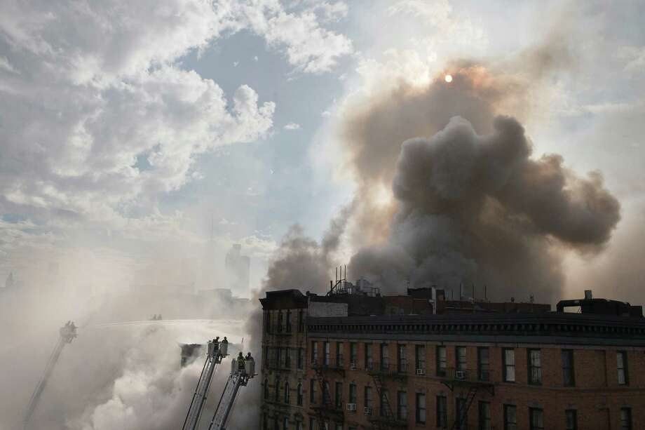 New York City firefighters work the scene of a large fire and a partial building collapse in the East Village neighborhood of New York on Thursday, March 26, 2015. Orange flames and black smoke are billowing from the facade and roof of the building near several New York University buildings. (AP Photo/John Minchillo) Photo: John Minchillo, FRE / Associated Press / FR170537 AP