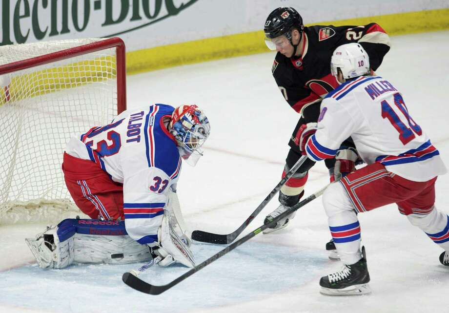 New York Rangers goalie Cam Talbot, left, deflects a shot from Ottawa Senators right wing Curtis Lazar, middle, as he is pressured by Ranger center J.T. Miller during the first period of an NHL hockey game Thursday, March 26, 2015, in Ottawa, Ontario. (AP Photo/The Canadian Press, Adrian Wyld) ORG XMIT: AJW102 Photo: Adrian Wyld / The Canadian Press