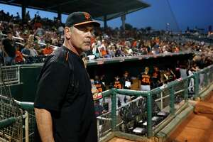San Francisco Giants manager Bruce Bochy stands in front of the team dugout prior to a spring training baseball game against the Cleveland Indians Tuesday, March 24, 2015, in Goodyear, Ariz. (AP Photo/Ross D. Franklin)