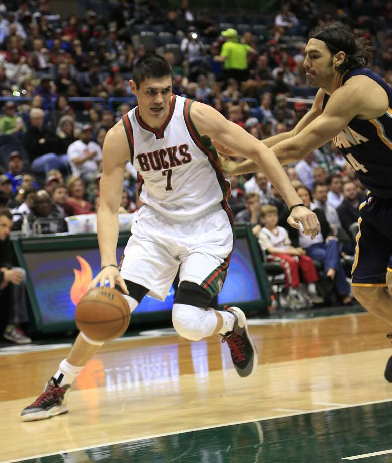 Milwaukee Bucks forward Ersan Ilyasova, left, drives to the basket against Indiana Pacers forward Luis Scola, right, during the first half of an NBA basketball game Thursday, March 26, 2015 in Milwaukee. (AP Photo/Darren Hauck) Photo: Darren Hauck, Associated Press