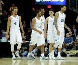 Kentucky's Andrew Harrison (5) is smiles along with his teammates — Trey Lyles (41), Dakari Johnson (44), Devin Booker (1), and Willie Cauley-Stein (15) — after Harrison scored on an acrobatic drive to the basket against West Virginia in the second half of the Wildcats 78-39 domination a Sweet 16 game in Cleveland.