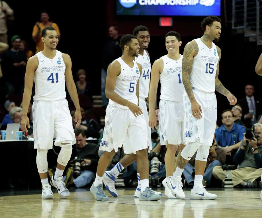 Kentucky's Andrew Harrison (5) is smiles along with his teammates — Trey Lyles (41), Dakari Johnson (44), Devin Booker (1), and Willie Cauley-Stein (15) — after Harrison scored on an acrobatic drive to the basket against West Virginia in the second half of the Wildcats 78-39 domination a Sweet 16 game in Cleveland. Photo: Charles Bertram / McClatchy-Tribune News Service / Lexington Herald-Leader