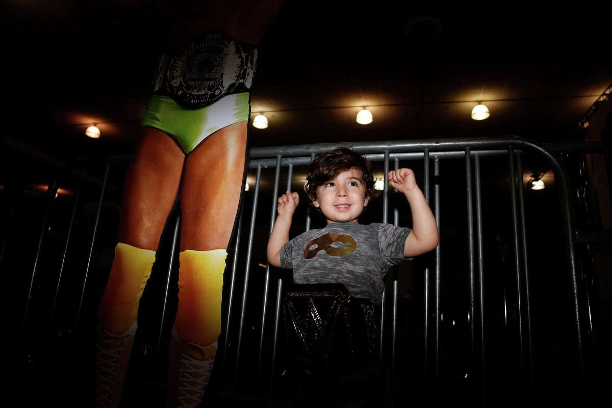 """Holden Guerrero, 2, of Portland, Ore., poses for his father near a cut out of Randy """"Macho Man"""" Savage."""