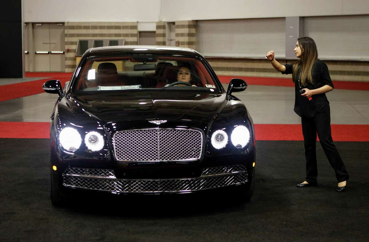 Bianca Gonzalez of Park Place Premier Collection parks a Bentley Flying Spur W12 as Amanda Tovar directs her in the High End section of the 2015 DFW Auto Show in Dallas on Monday, March 23, 2015. The base price of the Flying Spur was listed as $215,800. (Jim Tuttle/Dallas Morning News/TNS)