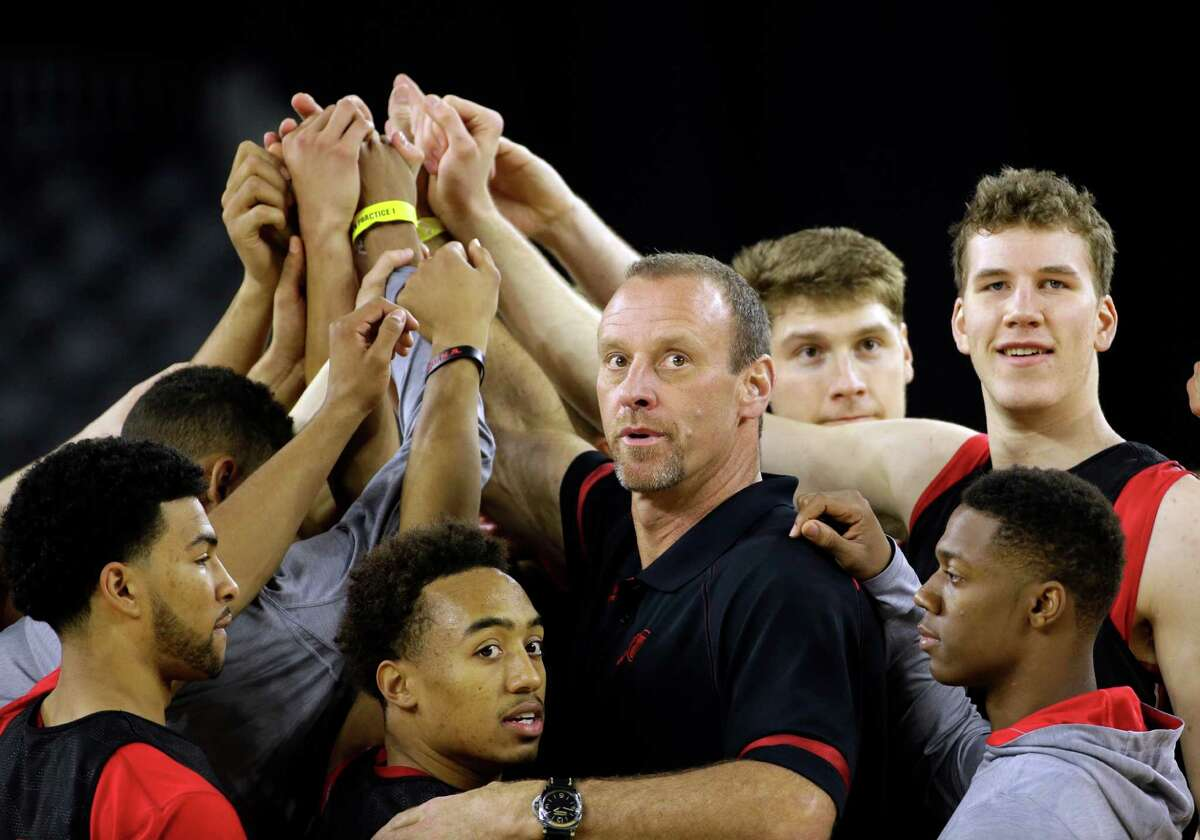 Utah head coach Larry Krystkowiak huddles with players during a practice session for a college basketball regional semifinal game in the NCAA Tournament Thursday, March 26, 2015, in Houston. Utah plays Duke on Friday. (AP Photo/David J. Phillip)