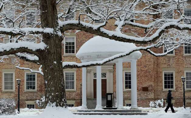 A pedestrian walks past the Old Well on campus at The University of North Carolina in Chapel Hill, N.C., Thursday, Feb. 26, 2015 after a winter storm dumped several inches of snow. (AP Photo/Gerry Broome) Photo: Gerry Broome, Associated Press / AP