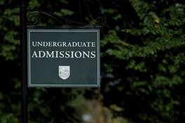 Students walk past a sign for undergraduate admissions at Dartmouth College the day before a Republican presidential debate sponsored by Bloomberg and The Washington Post held at Dartmouth College in Hanover, New Hampshire, U.S., on Monday, Oct. 10, 2011. The event presents the first debate of the 2012 political season focused solely on the economy. Photographer: Scott Eells/Bloomberg