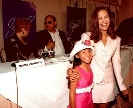 BEVERLY HILLS, UNITED STATES:  Becky Lee Meza (L), 9, and Jennifer Lopez (R) stand during a press conference in Beverly Hills, 18 June. The duo are the stars of the upcoming Warner Brothers Studios movie about deceased Tejano singer Selena.  Behind the actresses sit Selena's parents Marcella (L) and Abraham Quintanilla Jr. (R).                       AFP PHOTO  Tiziana SORGE Photo: TIZIANA SORGE, Getty Images / AFP