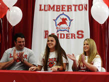 Lauren Glover, center, is flanked by father Dack and mother Melissa as she signs with Lamar on Thursday. Glover signed her letter of intent to play soccer for Lamar University on Thursday afternoon at Lumberton High School.  Photo taken Thursday 3/26/15  Jake Daniels/The Enterprise