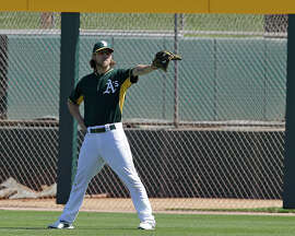 Oakland Athletics' Josh Reddick waves to a fan during practice prior to a spring training exhibition baseball game against the Chicago Cubs Tuesday, March 24, 2015, in Mesa, Ariz. (AP Photo/Ben Margot)