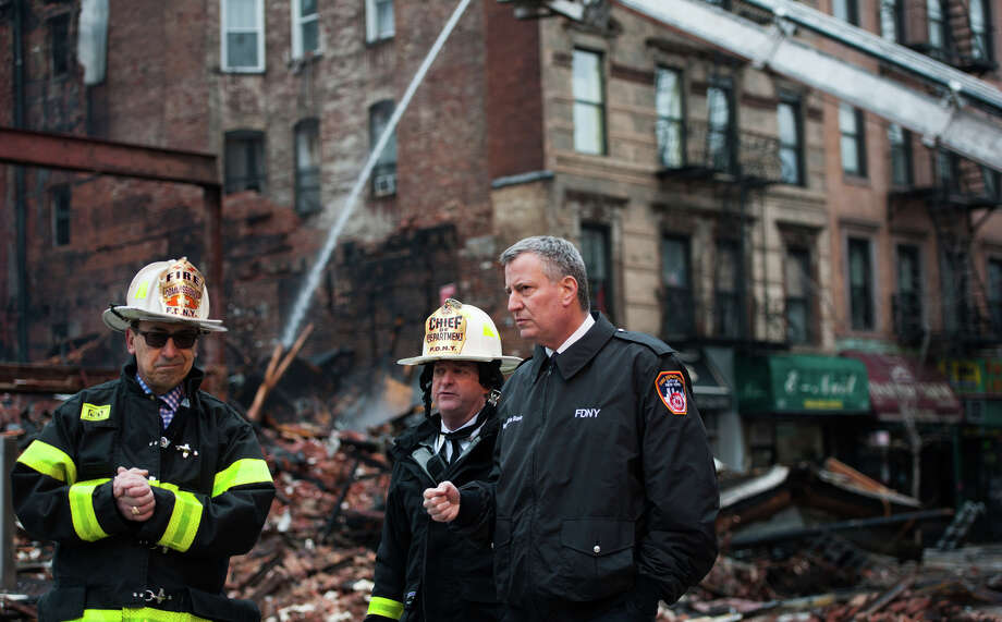 New York City Mayor Bill de Blasio (right) visits the site of an explosion and fire that leveled three apartment buildings and injured nearly two dozen people in the East Village. Photo: Pool / Getty Images / 2015 Getty Images