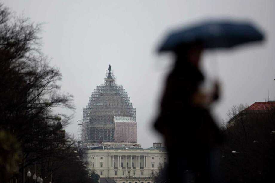 A pedestrian carries an umbrella while walking past the U.S. Capitol Building surrounded by scaffolding in Washington, D.C., U.S., on Friday, March 27, 2015. The U.S. Senate adopted a fiscal 2016 budget that calls for $5.1 trillion in spending cuts to achieve balance in 10 years, while avoiding proposals to partially privatize Medicare as many Republicans brace for re-election. Photo: Andrew Harrer / Bloomberg / © 2015 Bloomberg Finance LP