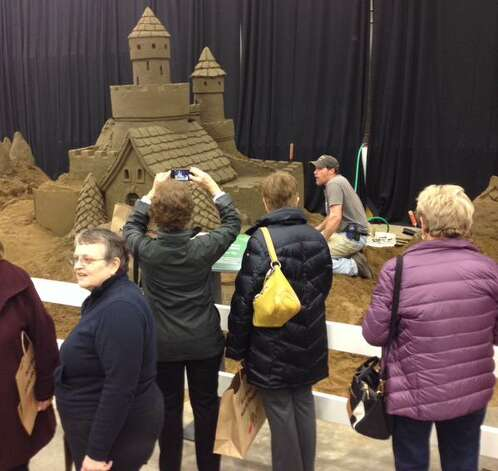 """The """"Sand Man"""" Phil Singer builds a sand castle at the Capital District Garden & Flower Show on Friday, March 27, 2015 at Hudson Valley Community College in Troy. The event continues through Sunday. (John Carl D'Annibale/Times Union)"""