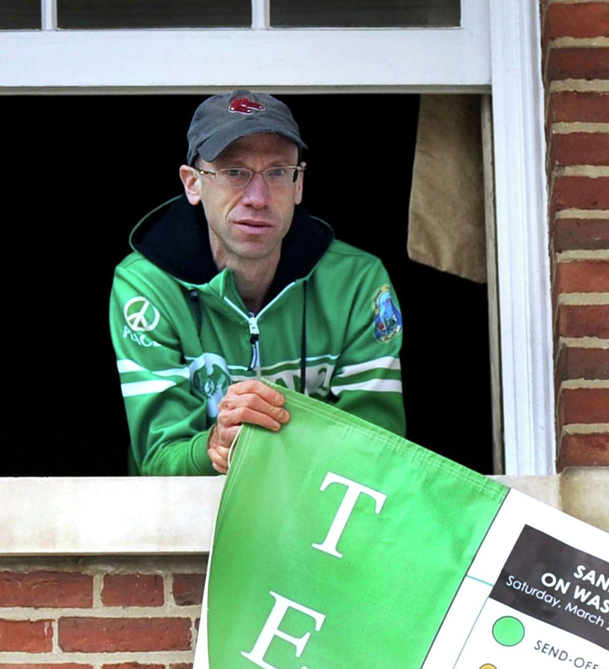 Monte Frank, the founder of the Sandy Hook Ride on Washington, hung a banner in preparartion for the Saturday morning send-off at the Edmond Town Hall that starts this year's ride. Friday, March 27, 2015.