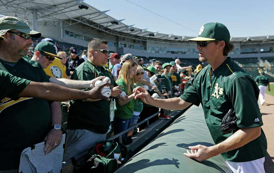 FILE - In this March 8, 2015, file photo, Oakland Athletics' Tyler Clippard, right, prepares to autograph baseballs prior to a spring training baseball game against the Chicago White Sox in Mesa, Ariz. The Oakland Athletics topped even their most trade-happy of days by making nine swaps involving 27 players in a wild offseason for Billy Beane and his front-office bunch. (AP Photo/Ben Margot, File) Photo: Ben Margot / Associated Press / AP