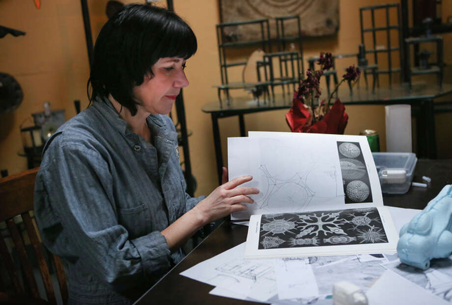 Kyrsten Mate leafs through sketches for their latest art car. Photo: Amy Osborne / The Chronicle / ONLINE_YES