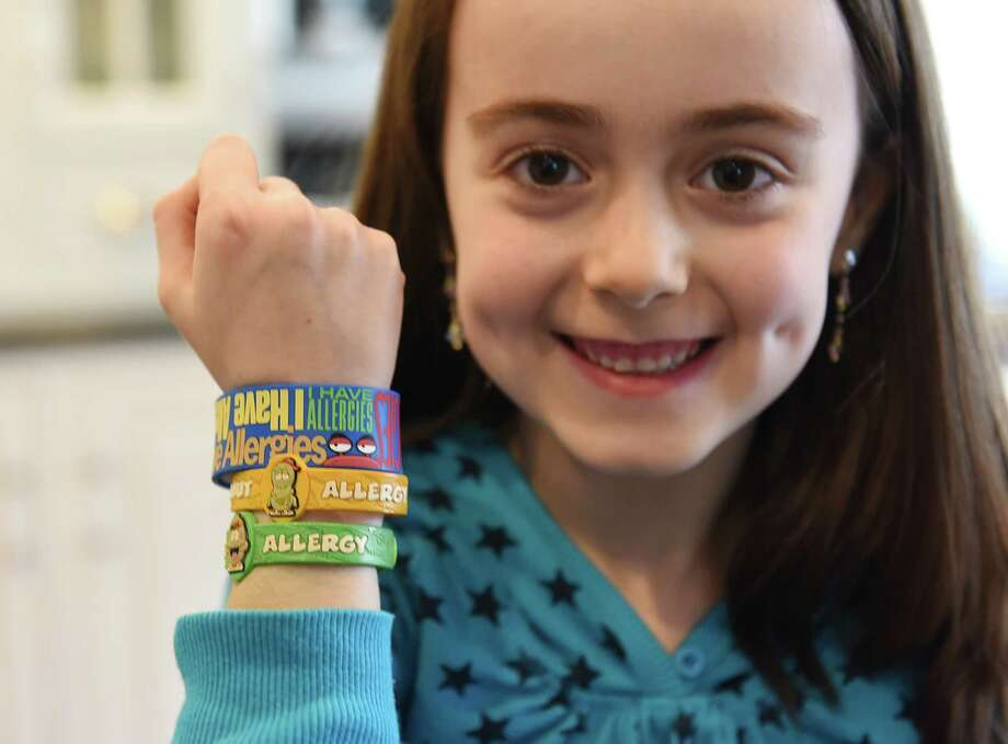Sophia Large shows her allergy wristbands at her home in the Glenville section of Greenwich, Conn. Sunday, March 15, 2015.  Katie, 13, and Sophia, 7, both have life-threatening food allergies and must be very cautious of the food they eat.  The Large family is happy with the strides that Glenville has made in recognizing food allergies and educating the community, but would like to see that same support throughout the rest of Greenwich. Photo: Tyler Sizemore / Greenwich Time